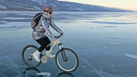 ağarmış : Woman is riding bicycle on the ice. The girl is dressed in a silvery down jacket, cycling backpack and helmet. Ice of the frozen Lake Baikal. The tires on the bicycle are covered with special spikes. The traveler is ride a cycle.