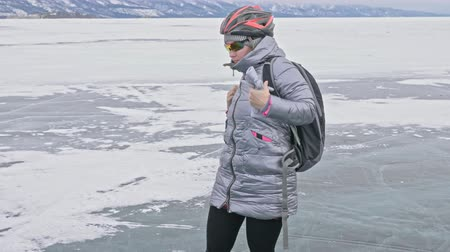 plecak : Woman is wearing sports equipment. The girl is dressed in a silvery down jacket, cycling backpack and helmet. Ice of the frozen Lake Baikal. The tires on the bicycle are covered with special spikes. The traveler is ride a cycle.