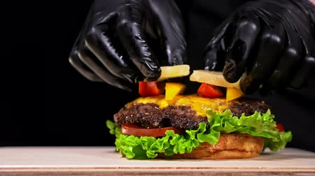 соленья : Burger is cooking on black background in black food gloves. Very luscious air bun and marbled beef. Restaurant where each burgers is cooked by hand. Put pineapple and sweet pepper. Not made ideal. Not conveyor. Looks real, loving hand made. Стоковые видеозаписи