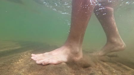 territorial : Underwater shot of feet walking on sandy ocean beach. The camera moves under the water. Stock Footage