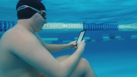timeout : The guy is reading an electronic book underwater. This is a special waterproof electronic device. You can read the text and show signs directly underwater. Stock Footage