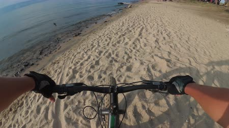 slough : Fat bike also called fatbike or fat-tire bike in summer riding. Driving on different surfaces of stones, sand, grass, mud. A view from the first person to the steering wheel, hands and road. Stock Footage