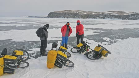 winter day : RUSSIA, OLKHON - FEBRUARY 28, 2018: Cyclists travelers from Poland ride ice on bicycles. Extremes cross Lake Baikal along its length. Route of the hike is more than 600 km. Weight of each bicycle along with the removal of more than 130 kg.
