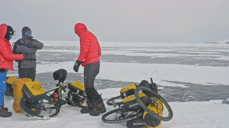 quad bike : RUSSIA, OLKHON - FEBRUARY 28, 2018: Cyclists travelers from Poland ride ice on bicycles. Extremes cross Lake Baikal along its length. Route of the hike is more than 600 km. Weight of each bicycle along with the removal of more than 130 kg.