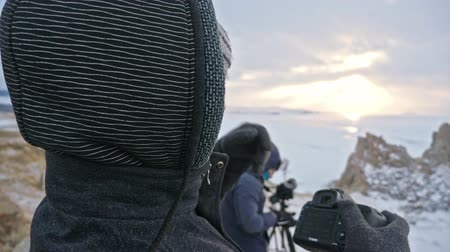 УВР : RUSSIA, OLKHON - MARCH 1, 2018: Photographer tourist watching and taking photos of famous sunset view in the Lake Baikal. Men takes pictures of camera canon 5d mark 3.