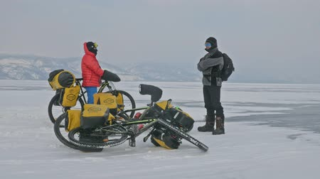 сосулька : RUSSIA, OLKHON - FEBRUARY 28, 2018: Cyclists travelers from Poland ride ice on bicycles. Extremes cross Lake Baikal along its length. Route of the hike is more than 600 km. Weight of each bicycle along with the removal of more than 130 kg.