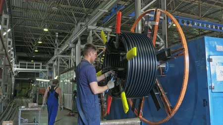 corrugated : RUSSIA, ANGARSK - JUNE 8, 2018: Roll threading coil pipe. Manufacture of plastic water pipes to the factory. Process of making plastic tubes on the machine tool with the use of water and air pressure. Stock Footage