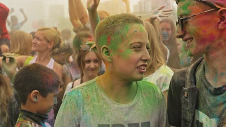 RUSSIA, IRKUTSK - JUNE 27, 2018: Happy young people dancing and celebrating during Music and Holi Festival Of Colors. Crowd of people colored powder and having fun in arena.