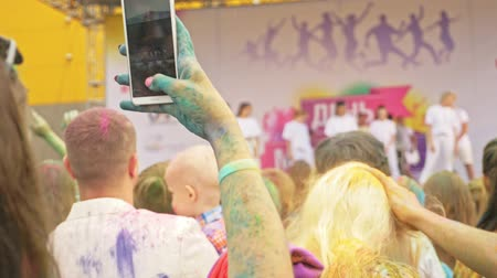 tendo : RUSSIA, IRKUTSK - JUNE 27, 2018: Happy young people dancing and celebrating during Music and Holi Festival Of Colors. Crowd of people colored powder and having fun in arena.