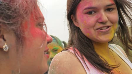concert crowd : RUSSIA, IRKUTSK - JUNE 27, 2018: Happy young people dancing and celebrating during Music and Holi Festival Of Colors. Crowd of people colored powder and having fun in arena.