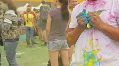 cultura juvenil : RUSSIA, IRKUTSK - JUNE 27, 2018: Happy young people dancing and celebrating during Music and Holi Festival Of Colors. Crowd of people colored powder and having fun in arena.