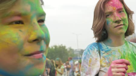 worshipers : RUSSIA, IRKUTSK - JUNE 27, 2018: Happy young people dancing and celebrating during Music and Holi Festival Of Colors. Crowd of people colored powder and having fun in arena.