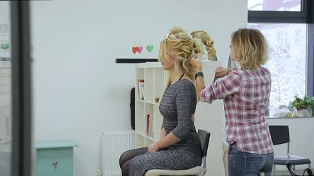 bob hairstyle : Hairdresser makes hairstyle young blonde woman in a beauty salon Stock Footage