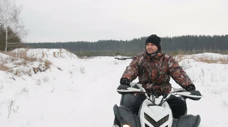 quad bike : a young guy in a black hat and camouflage jacket sitting on the ATV and ready to ride. Movement on Steadicam. Slowmotion.