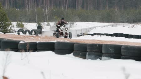 quad bike : A young guy in a black hat and camouflage jacket extreme cornering snow track with the race on the ATV. From the wheels flying dirt and snow. Slowmotion.