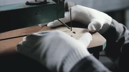 fizet : hands in white gloves jigsaw to cut a wooden workpiece, the symbol of bitcoin
