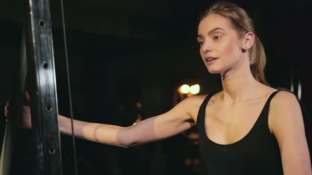 capa dura : a pretty slender blonde in a black t-shirt and blue leggings trains the back of the thigh in a dark fitness club, during the exercise the girl breathes heavily and smiles, the movement of the camera on the steadicam