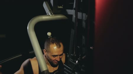 sağlam : guy trains shoulders at the trainer in the dark gym