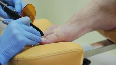 pedikür : hands of a doctor of Podiatry is heated by the device the nail of male patient in the beauty salon, close-up