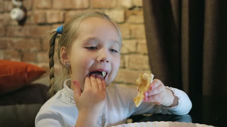 iştah : little girl in a cafe eats pizza, licks her fingers. Concept: you will lick your fingers