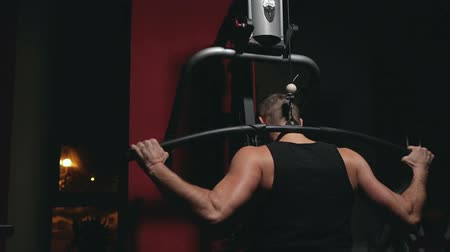 sağlam : guy trains shoulders at the trainer in the dark gym, the movement of the camera on the Steadicam