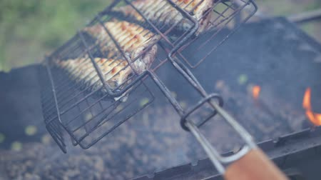 seafood dishes : grill with fish turns over on the grill, there is smoke