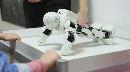 gimnazjum : little robot is engaged in physical education at the exhibition, the child repeats the exercise