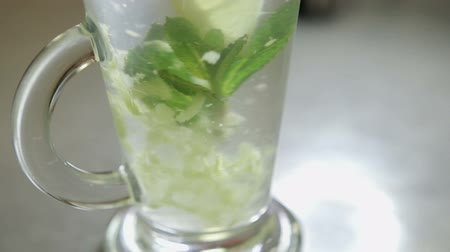 homeopati : spoon stirring his tea with mint and lemon in a transparent glass, shot close-up Stok Video