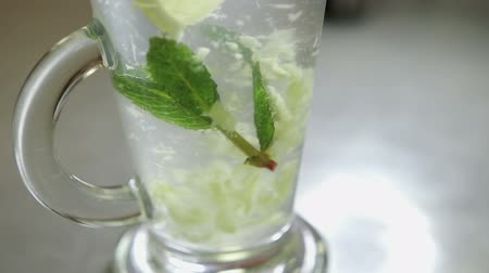 homeopathic : spoon stirring his tea with mint and lemon in a transparent glass, shot close-up Stock Footage