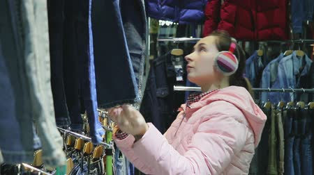 trousers : young woman with headphones on the ears selects the pants in the store jeans