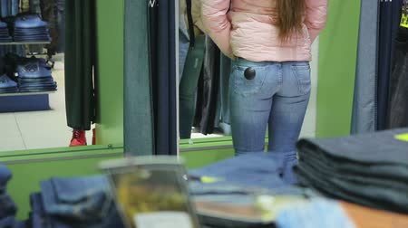 trousers : young woman tries on pants in the jeans shop, close-up