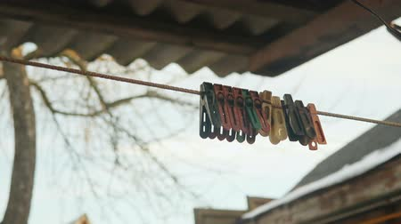 прищепка : old colored clothespins on a clothesline against the evening sky Стоковые видеозаписи