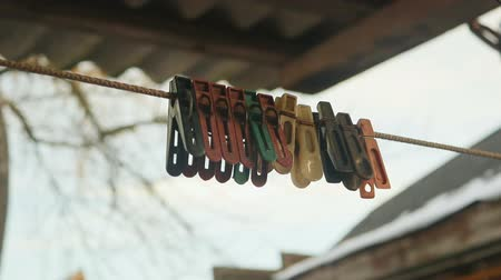 braçadeira : old colored clothespins on a clothesline against the evening sky Vídeos