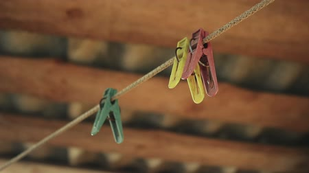 clothesline : old colored clothespins on the clothesline on wooden background roof of the shed Stock Footage