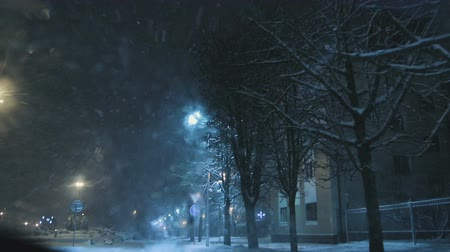 snowy background : Bad weather, rain and sleet on the background of night lights. Snowfall in the city at night. The view from the car window Stock Footage