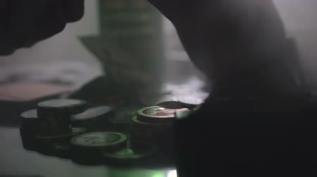 as : Poker game in a smoky, dark casino. On the table chips, alcohol, cards, money. Close up Wideo