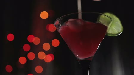 lyme : hand mixes the red cocktail with a tubule in a Martini glass. In a nightclub on the background of lights