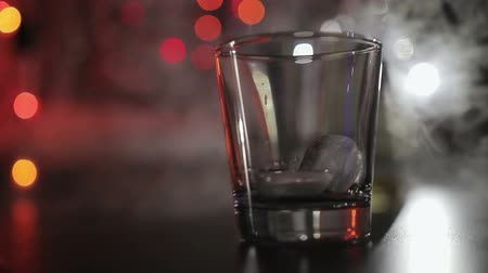 karczma : two pieces of ice fall into a whiskey glass. Glass stands against the background of the night club lights and smoke