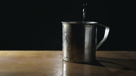 хром : Iron mug with handle is on a dark background, in a bowl filled with water. Close up. The concept of a Russian prison
