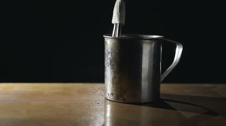 хром : old metal mug stands on a table on a dark background, in the dishes falls spiral iron boiler with an electric wire