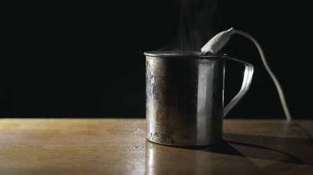 хром : Old metal mug is on the table on a dark background, in the dishes is a spiral iron boiler with an electric wire, the water is heated and boils. Close up