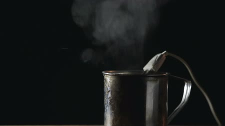 хром : Old metal mug is on the table on a dark background, in the dishes is a spiral iron boiler with an electric wire, the water is heated, boiled and splashed out. Steam rises from the water. Risk of burn and fire. Close up
