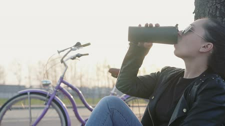 ciclismo : pretty girl with dark hair, wearing a leather jacket and sunglasses sitting on the grass near a tree and drinking coffee out of thermal mugs at sunset. In the background vintage bike. The movement of the camera on the Steadicam