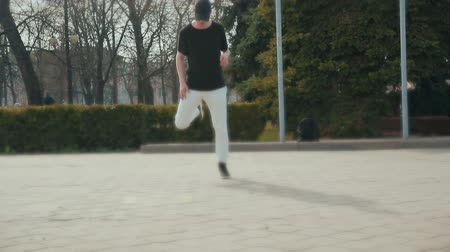 akrobatikus : Guy in black shoes and grey pants, warming up before a dance performance. Steadicam shot Stock mozgókép
