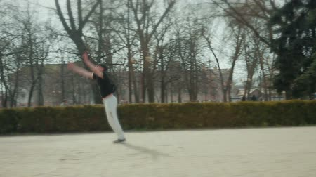 cep şişesi : Modern young guy performs a flip trick on the city square, in the background passers-by people. Steadicam shot