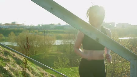 a healthy lifestyle : Young pretty sportswoman is engaged in fitness in nature. The girl performs physical exercises on the stairs of the automobile bridge. Steadicam shot Stock Footage