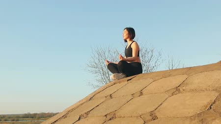 nogi : Young pretty girl is engaged in meditation sitting on concrete slabs. Steadicam shot Wideo