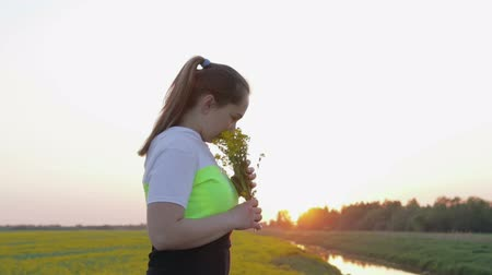 изнасилование : A young woman with a bouquet of flowers from canola walks at sunset. Steadicam shot