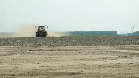 plantio : A tractor with an agricultural machine processes the soil, a lot of dust rises. The problem of soil erosion