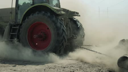 ekili : A tractor with an agricultural machine processes the soil, a lot of dust rises. The problem of soil erosion